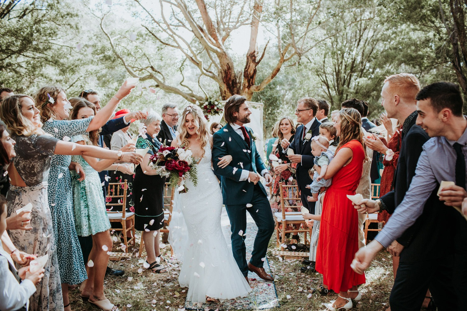 Couple exiting the aisle with rose petals thrown at them