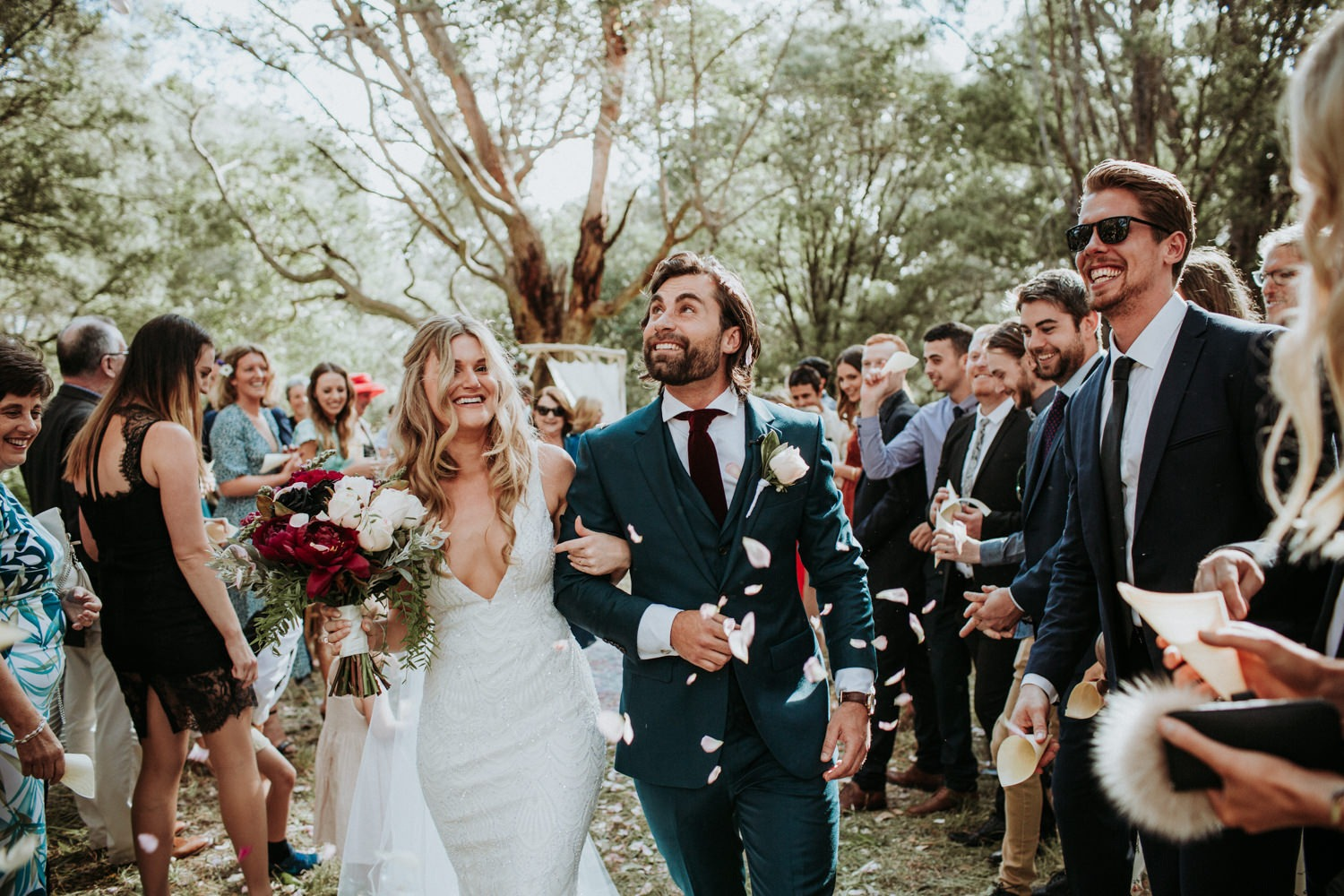 Byron Bay Couple walking down the aisle after the ceremony. Rose petals thrown at them