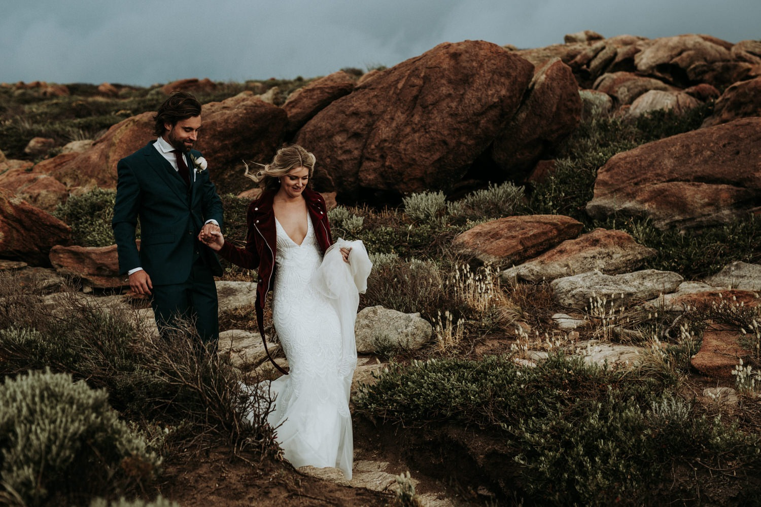 Eclectic couple walking near the coast for their wedding photos