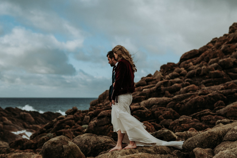 Couple walking on rocks near the beach in Byron Bay