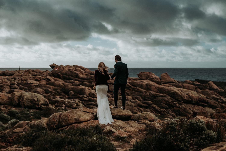 Couple walking on beautiful rocky beach near Byron Bay