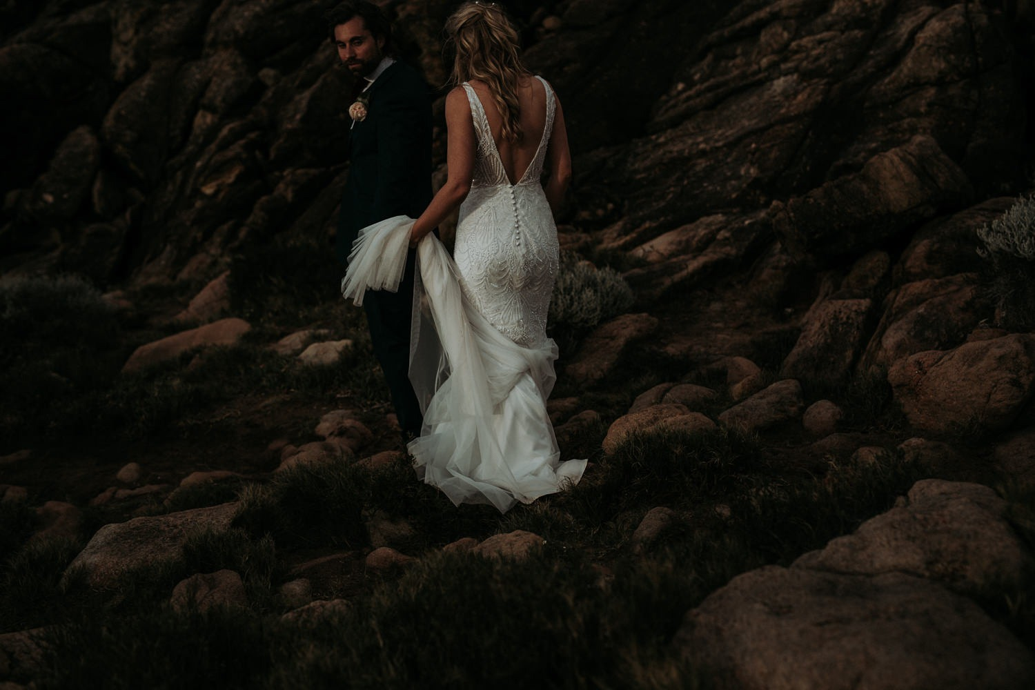 Bride and groom walking together during their wedding photos on rocky beach near Byron Bay