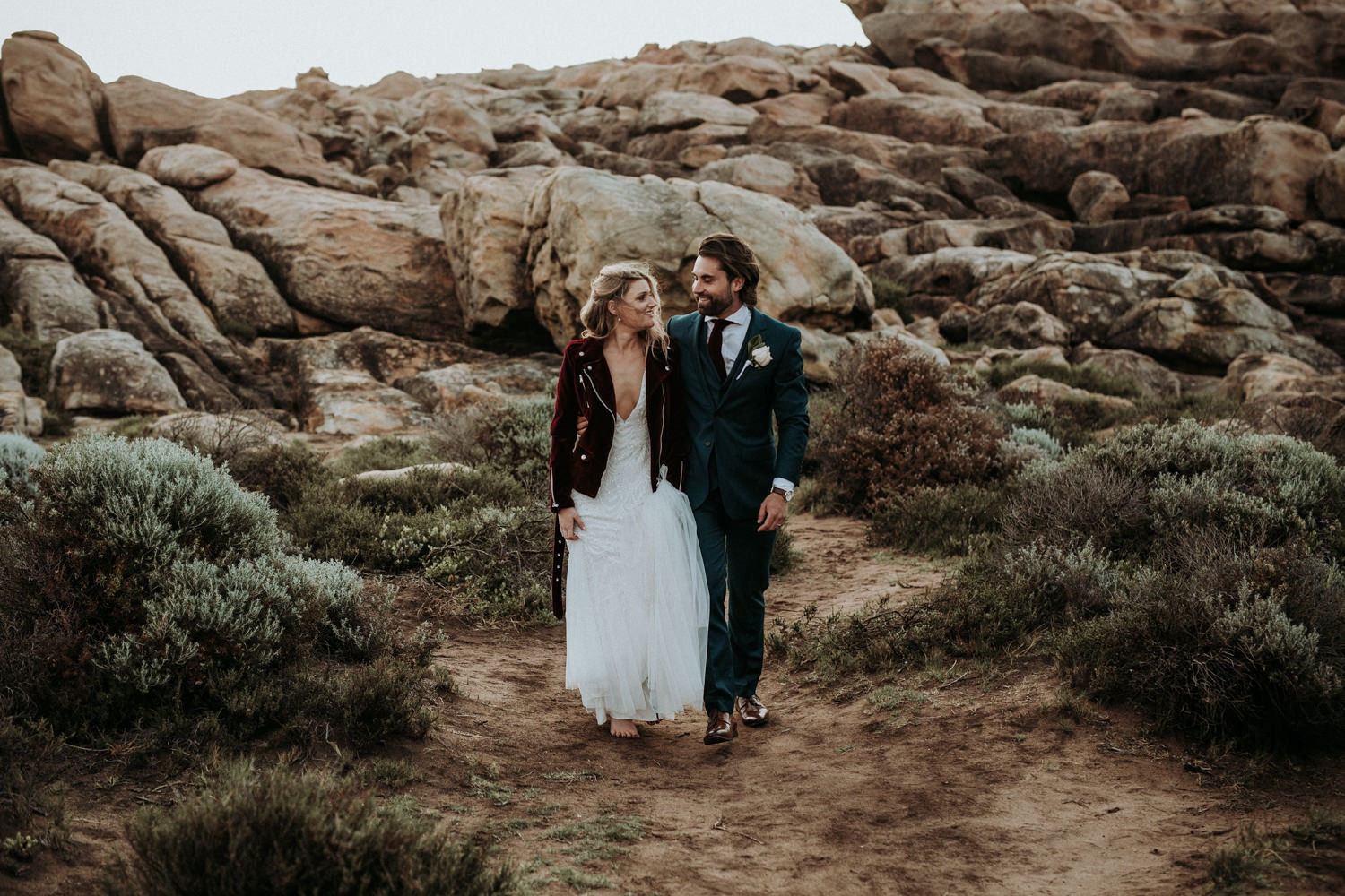 Couple portrait of eclectic couple on rugged beach near Byron Bay. Bride wearing red velvet jacket.