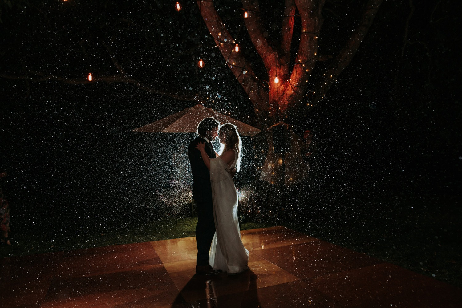 Photo of couple during their first dance in the rain. Rustic Byron Bay Wedding.