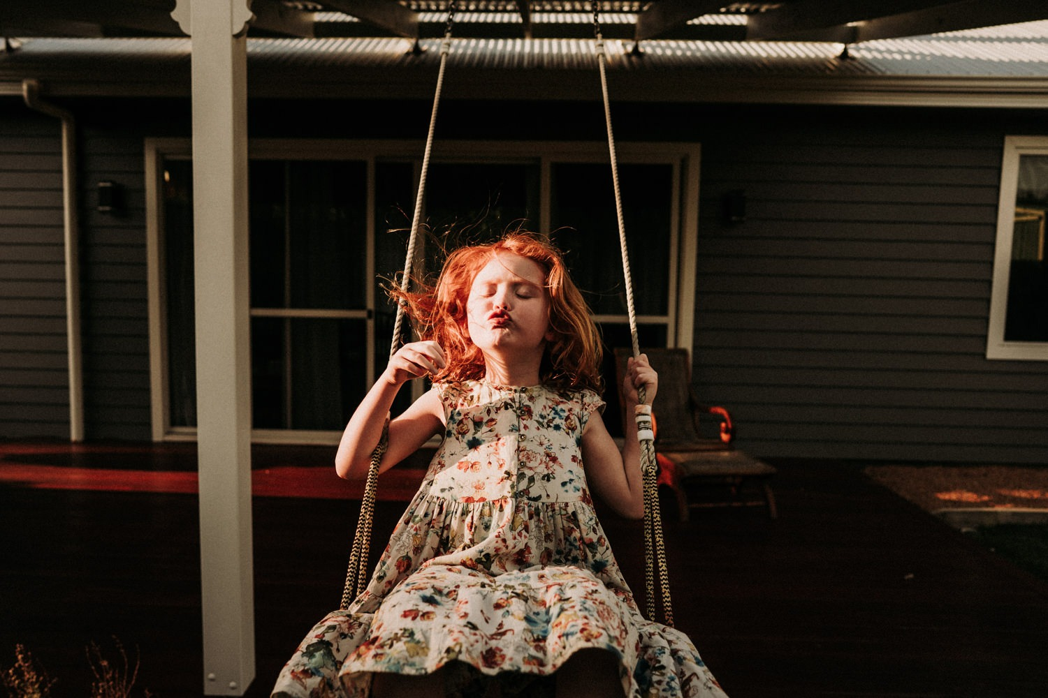 Candid photo of young girl on her swing at home in Byron Bay