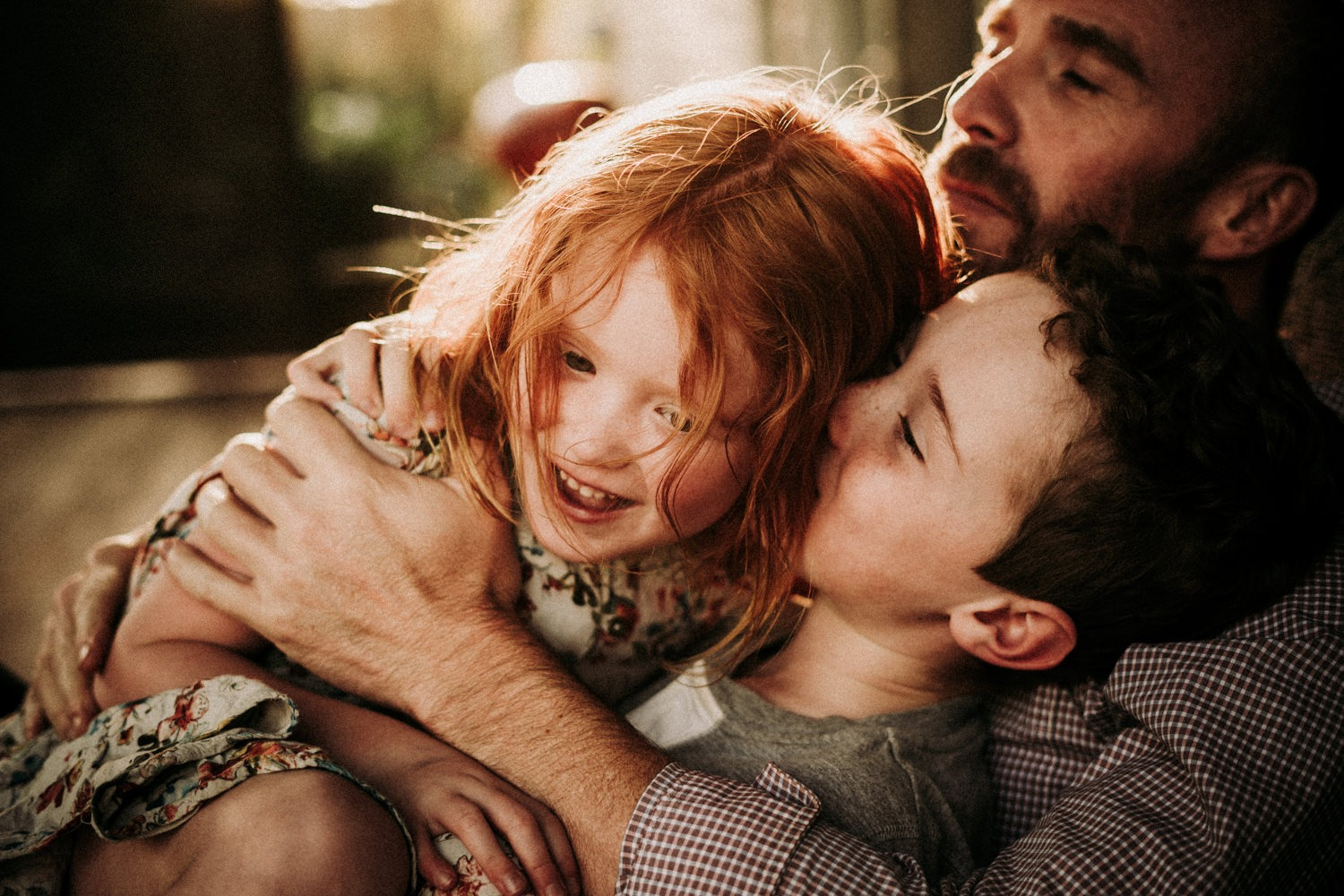 Golden light shining through the red hair of young girl whilst having cuddles with her family near Byron Bay